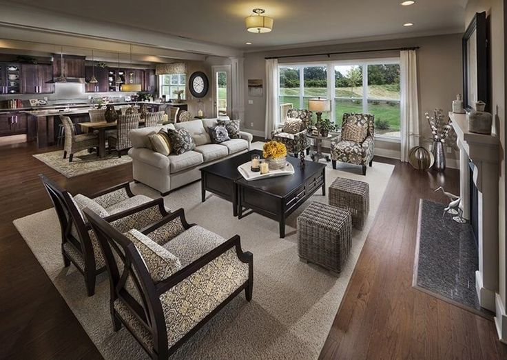 This lovely contemporary open-concept living room connects to the dark wood kitchen with a large rustic dining table with wicker chairs. Enormous windows let in tons of natural light.