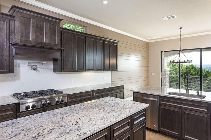 Transitional kitchen with espresso cabinets, cabinet venthood, pot filler.