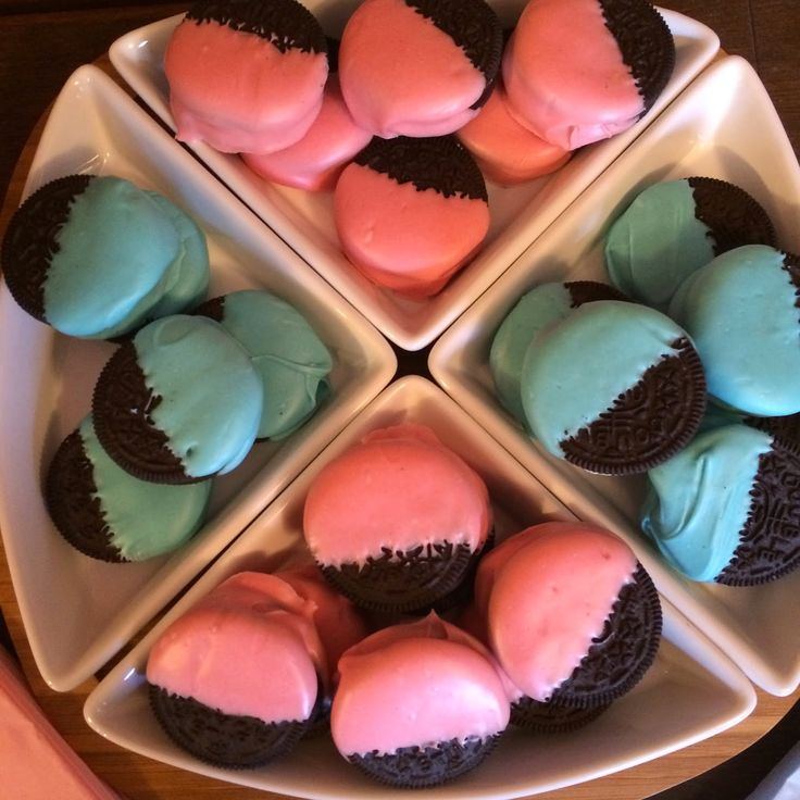 Blue and Pink Dipped Oreos.  A super easy dessert for a gender reveal party.  Just melt white chocolate in two bowl, color one bowl pink and the other bowl blue, dip the oreos in (I just dipped half) and allow to harden on a baking sheet lined with wax paper.  #genderrevealparty