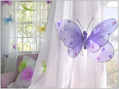 Attach the butterflies to the curtains. If they are not strong enough, how about hanging them from colourful ribbon from the curtain rod at different heights so they seem part of the curtains