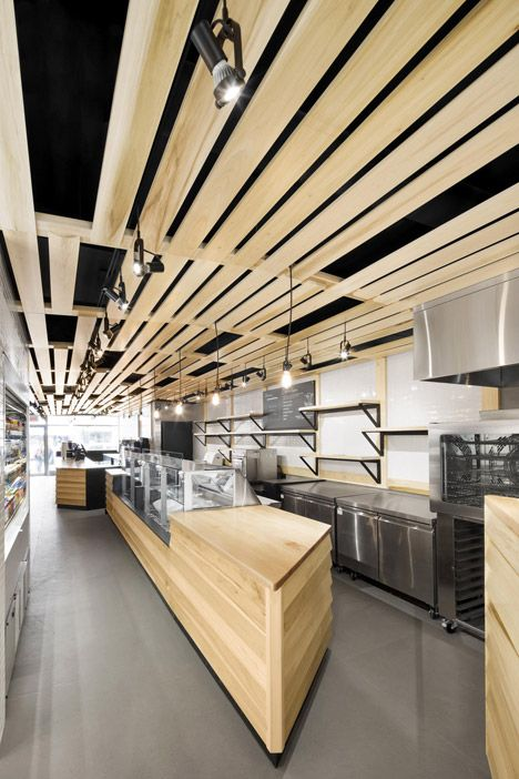 Wooden planks add warmth to the otherwise monochrome interior of this bakery and coffee shop.