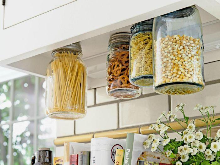 Печенье, специи и крупы удобно хранить в обыкновенных стеклянных банках, прикрученных к нижним частям полок и шкафчиков.