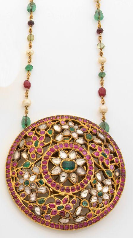 Pendentif broche en or jaune ajouré, de forme circulaire, composé de motifs de fleurs, pavés de cabochons de rubis et d'émeraudes et de diamants taille indienne. Travail des Indes de la fin du XIXe siècle. Photo Tajan