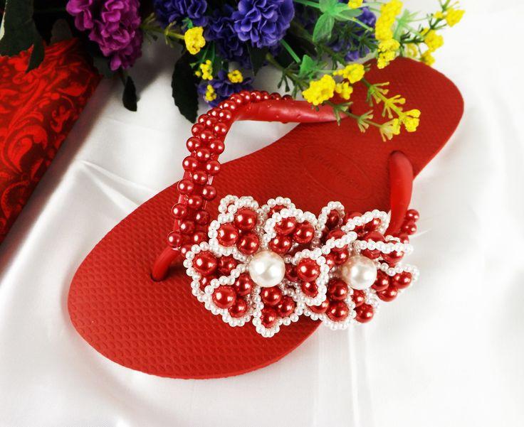Chinelo Havaianas personalizado com um bordado simples de pérolas e lindas flores vermelhas na tira.  Esse chinelo da foto foi feito no modelo Slim(tira fina) da Havaianas mas pode ser feito também no modelo Top(tira larga).  Somente sob encomenda, o prazo para confecção é de 5 dias úteis após a ...