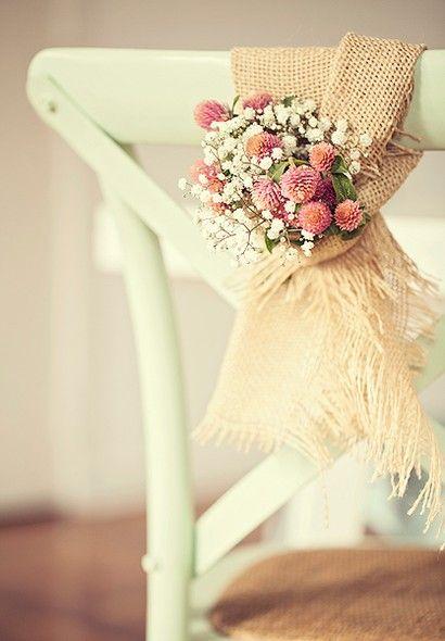 Uma maneira charmosa de receber, o arranjo de cadeira foi feito de juta com as flores perpétua e mosquitinho.