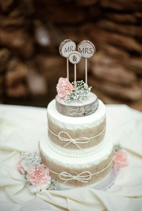 Brides: A Burlap-Wrapped Fall Wedding Cake with Flowers and Monogrammed Topper. A three-tiered rustic cake wrapped in burlap and twine, with a tree bark-inspired cake topper and fresh pink flowers by The Crown Room.