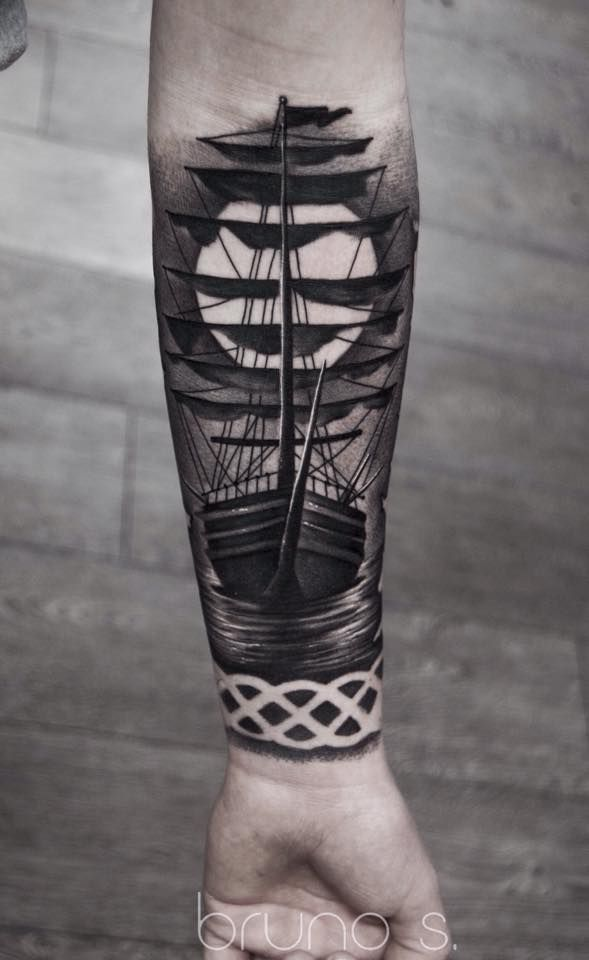 Black and grey ship tattoo with celtic band in negative