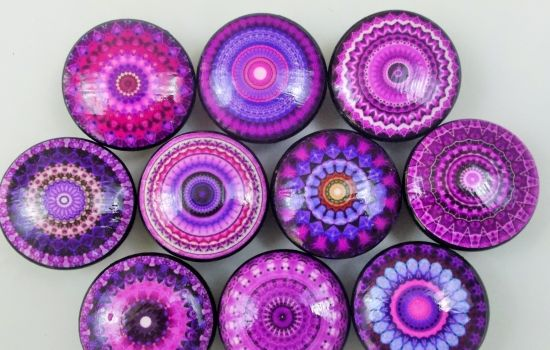"""Set of 10 purple mandala print wood knobs are 1.5"""" wide and have been painted black with a decoupage mandala pattern. Sealed with a triple coat gloss finish so these knobs are durable enough for everyday use on your cabinets or furniture. Mounting screws included, these wood knobs feature a brass insert to ensure a secure fit when attaching the enclosed screws."""