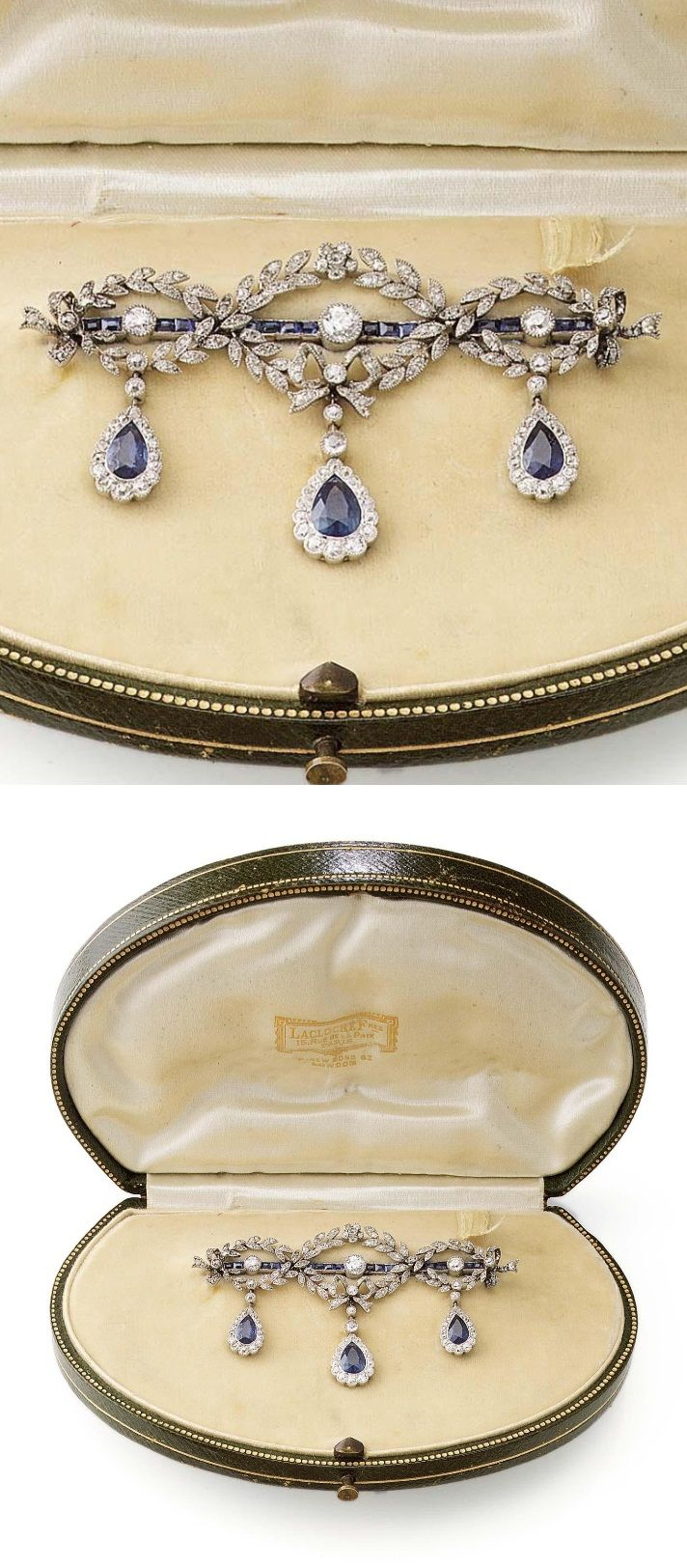 A BELLE EPOQUE SAPPHIRE AND DIAMOND BROOCH, CIRCA 1915. The calibré-cut sapphire and circular-cut diamond bar brooch, decorated with foliate and garland diamond swags, suspending three sapphire and diamond cluster pendants, assay marks to the pin and brooch fitting, vaguely numbered, traces of solder, accompanied by a fitted case by La Cloche Fres, Paris. #BelleÉpoque #brooch