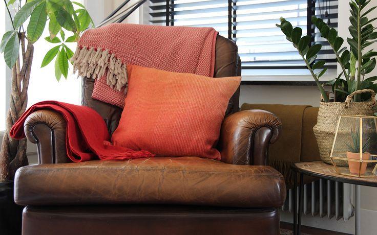 Met kussens en plaids in warme kleuren haal je de herfst in huis. Verkrijgbaar bij webshop Ookinhetpaars.