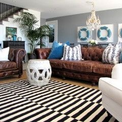 brown leather couch + gray walls + black & white striped rug