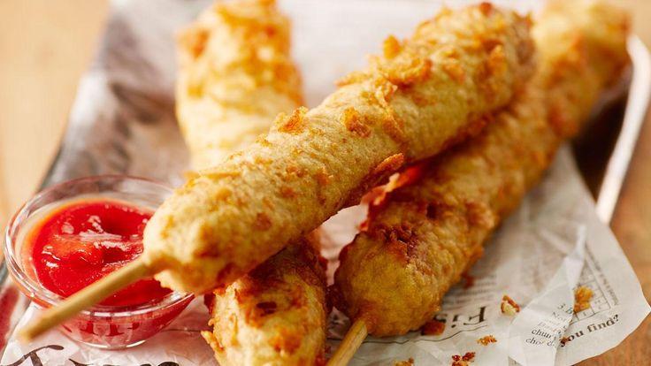 Corn dogs komen van origine uit Amerika. Het is een hot dog die door een beslag van o.a. mais en karnemelk gehaald wordt en vervolgens gebakken wordt in olie. Voor een extra textuur hebben we cornflakes aan het recept toegevoegd.