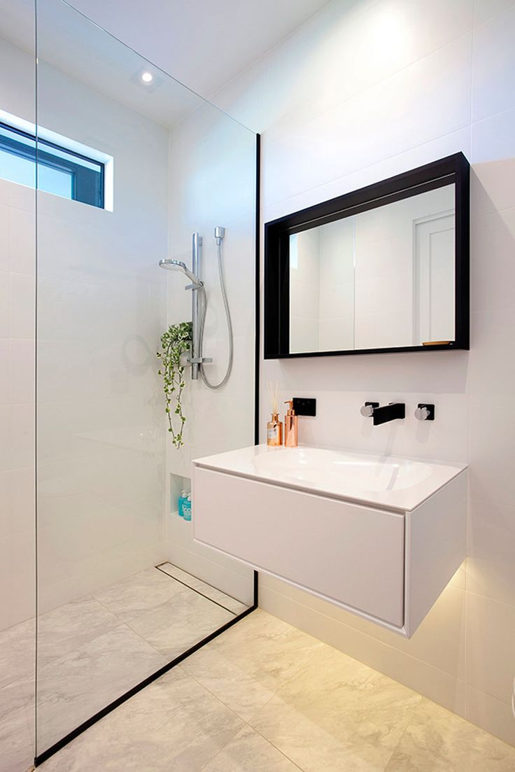 Modern small bathroom with walk in shower and glass panel