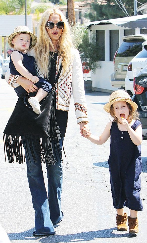 Rachel Zoe wears a black top, embroidered jacket, fringe bag, flare jeans, and retro sunglasses