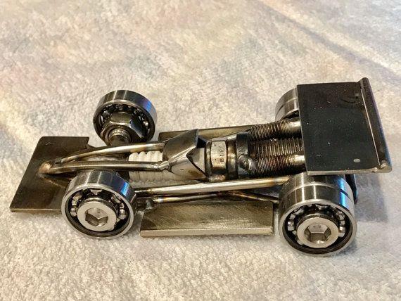 Cette voiture de course est une sculpture d'art basée sur une voiture Indy ou une voiture d'une course formule. Il est fait avec une bougie comme le corps, la seule roulements roues avant et le double sur l'arrière, cadre en acier inoxydable et aile et spoiler et d'échappement. C'est tout à la main en tig soudé par mes soins. Toutes les pièces sont faites dans ma boutique. Nous pouvons couche claire de cette voiture sans frais supplémentaires si vous voulez.  «Vous êtes à la recherche d'un…