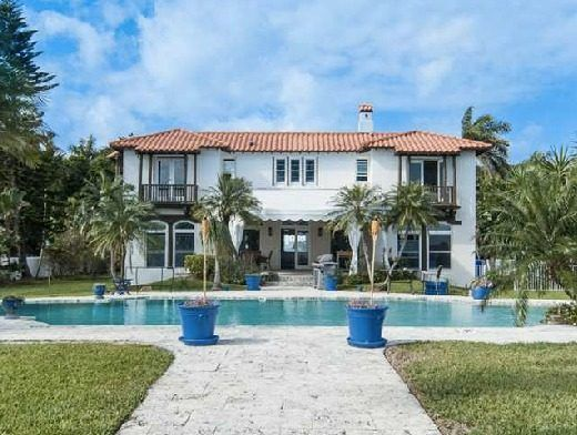 This Historic home has white stucco exterior, Spanish tile roofing, balconies, a chimney and a beautiful pool. Click through to see more images of this Miami house.