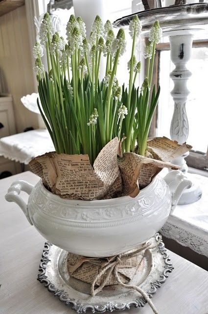 blooming flowers in a iron stone tureen~lovely! also like old newsprint in the tureen