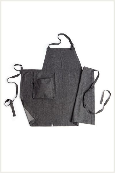 """This soft denim apron has a utility hanging pocket with a convenient loop for your wine key. Soft black denim Bar tack details Fabric denim ties 34"""" wide at waist 35"""" long Made in the USA of imported goods Black Denim 