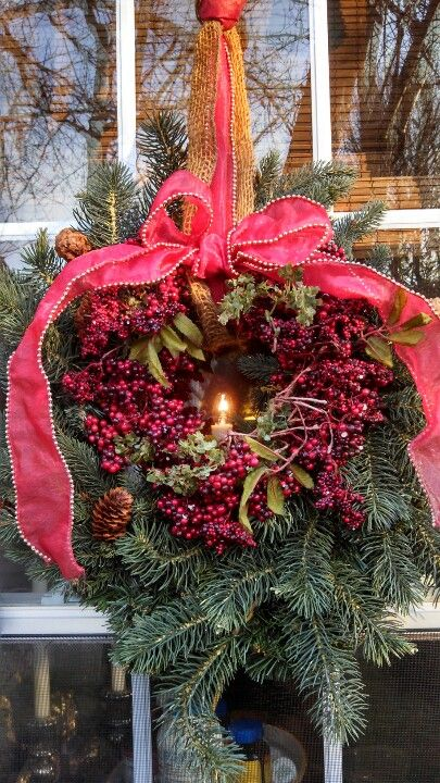 My kitchen window with beautiful Christmas wreath and candlelight peeking through~Leslie Meddings