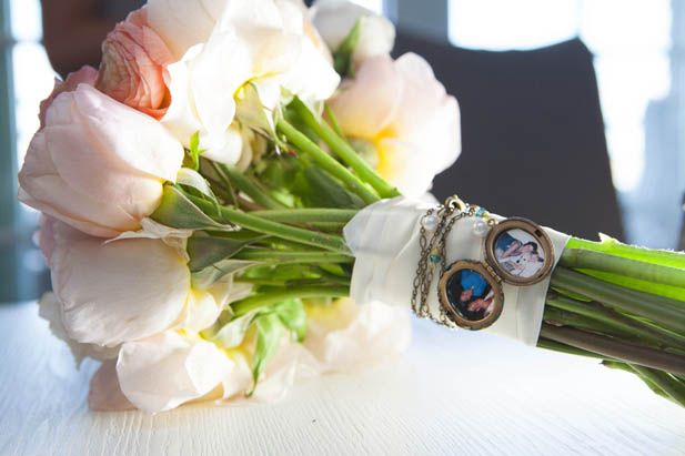 Locket with family photos wrapped around the bride's bouquet stem