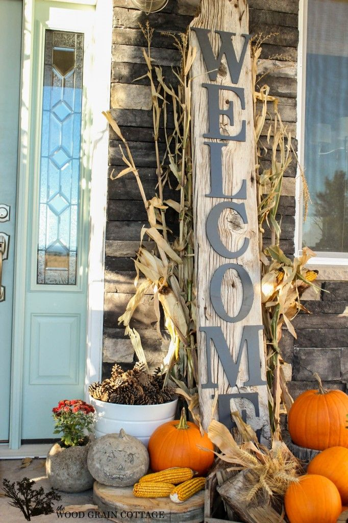 Fall Front Porchwith a large rustic welcome sign, cornstalks, pumpkins, and pine cones