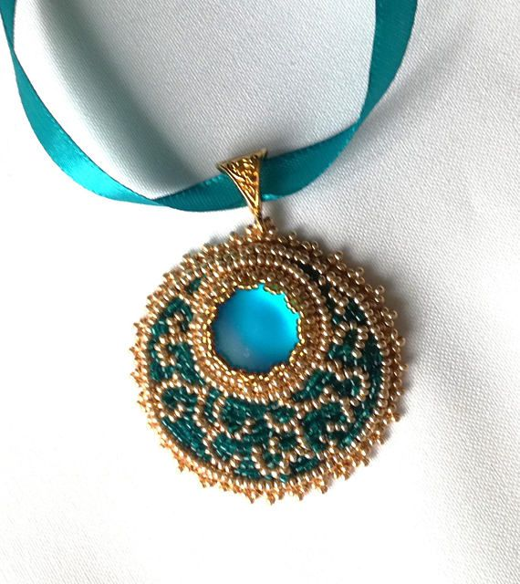 Hand Embroidered Beaded Pendant  - the pendants has a cabachon center piece - the pendant is decorated with Japanese beads.  - the pendant has a ribbon necklace of 27.5 inches / 70 cm. The rebons length can be changed as per request  - pendants length: 2.55 inches / 6.5 cm; widith: 1.96 inches / 5 cm The pendant is delivered in an organza jewelry bag.  It is a great gift idea, a birthday or anniversary present.