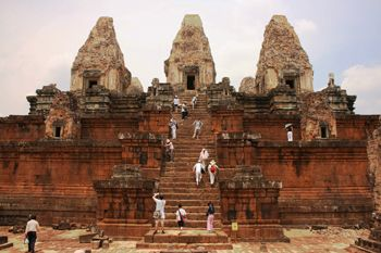 "Pre Rup  Angkor, Cambodia dedicated in 961/962  The state temple of Rajendravarman (944-968) is similar in plan (quincunx) and dimensions (roughly 400' x 400') to East Mebon, except of course there is no water. The temple's name is pronounced ""PRY ROOP"" (""OO"" as in ""loop""). This is a photo of the west face of the temple. The outer enclosure wall is constructed of laterite, with contrasting sandstone used for the windows and gate. Beyond the enclosure, a high central platform supports the…"