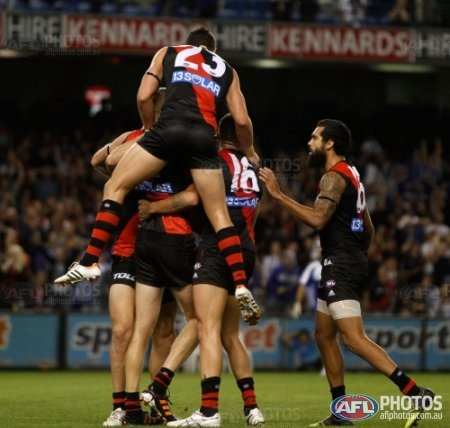 Essendon players celebrate their victory during the AFL Round 01 match between the North Melbourne Kangaroos and the Essendon Bombers at Etihad Stadium, Melbourne. (Photo: Greg Ford/AFL Media)