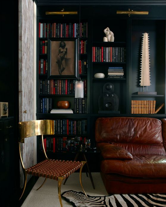 The Home Decor Essentials Every Modern Man Needs Mix of textures - worn leather, woven leather, brass, unfinished doors with black matte shelving. pinned by www.fioriinteriordesign.com