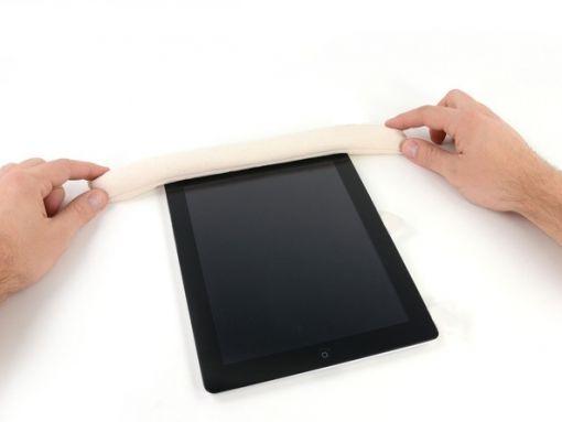 Schritt 11 -       Bevor Sie das erste Plektrum von der unteren Ecke des iPad entfernen, drücken Sie ein zweites Plektrum unter dem rechten Rand der Frontscheibe. Dadurch wird der Klebstoff nicht erneut anhaften.      Stecken Sie den iOpener wieder in die Mikrowelle und legen Sie es auf den oberen Rand des iPad.