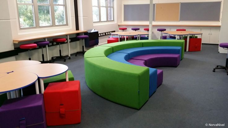 Colorful classroom with Rainbow tiered seating for group instruction and presentation and Pac tables with Miss-Shape ottomans from NorvaNivel.
