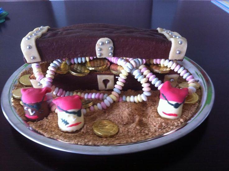 Rührkuchen mit Schokolade überzogen, quer durchgeschnitten, mit Marzipan und silberperlen verziert und dann gefüllt! Der Sand ist aus Vollkorn butterkeksen gemacht und die Piraten sind mini mohrenköpfe!