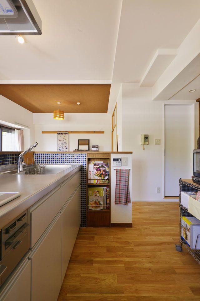 築15年の中古マンションリノベ、マンションリノベーション事例。お気に入りのダイニングテーブルが映える、和モダンのリビング。料理好きなので、キッチンにこだわりたいというご希望がありました。壁付けだったキッチンをオープンなカウンターキッチンに。カウンターはお客様のご希望を取り入れ、収納棚や飾り棚を組み込んだオリジナルデザインです。新居のために購入したお気に入りの無垢のテーブルに合わせ、床はナラ材を選びました。  リビング隣の和室は仕切りをなくし、リビングとつなげて広々と使えるように。ポイントに障子パネルを入れ、和の雰囲気を演出しています。 寝室やトイレなど、各部屋の壁は一面のみアクセントクロスを入れました。また、リビング以外の部屋の床はすべて天然素材のコルクタイルにしています。 玄関も、Sさんがお持ちの下足棚が入るようにたたきの部分を広げるなど、お客様の好みを最優先にした、こだわりの住まいです。