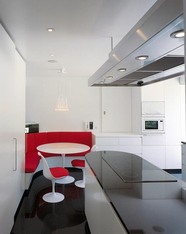 cuisine avec meubles blancs et plan de travail laqu noir coin repas avec banquette rouge