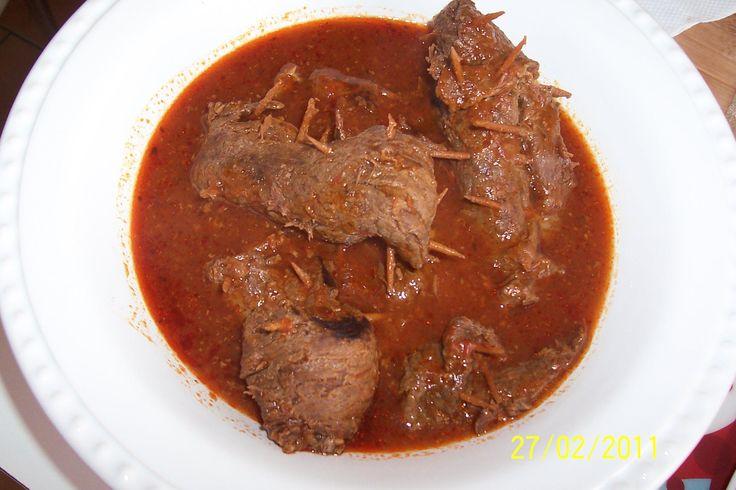 6 bifes grandes de coxão mole sem rasgos e sem gordura  - Amaciante para carnes com tempero completo Kitano  - 1 cebola pequena picadinha  - 2 colheres de sopa de azeite  - 1 cenoura média cozida picada  - 6 cogumelos picadinhos  - 6 tiras de bacon bem magrinha  - Azeitonas verdes picadas  - 1/2 sachê de molho de tomate  - 1 caldinho de carne Knorr  - Palitos de madeira  -