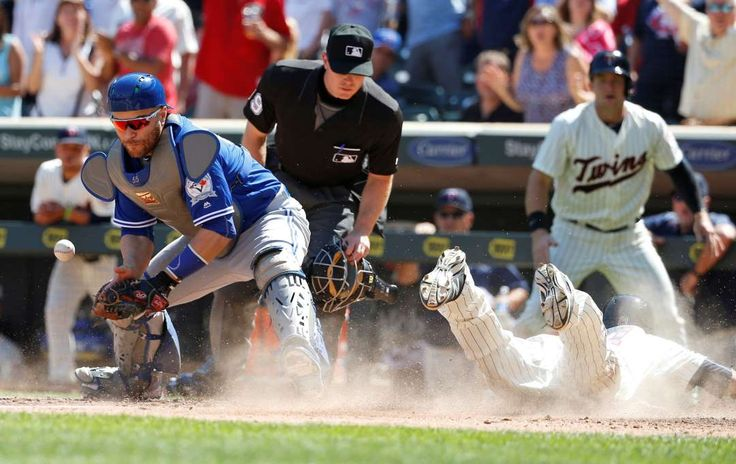 Goof-up:    Darin Mastroianni, right, of the Minnesota Twins scores on a double by teammate Danny Santana as Toronto Blue Jays catcher Russell Martin, left, bobbles the throw from right field during the eighth inning in Minneapolis on May 21. The Twins won 5-3.