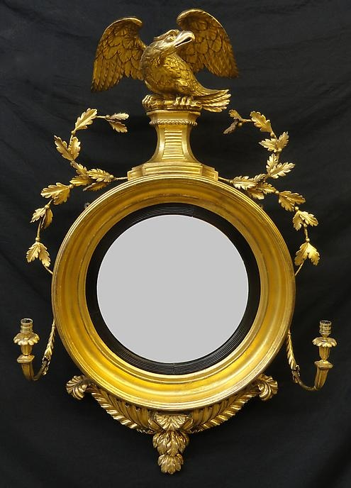 "A Regency Giltwood Convex Mirror,     CIRCA 1800,     Height: 49"" Width: 30"".         With a finely carved crest incorporating a spread-winged eagle, above laurel swags and candlearms; the apron carved with tied ropes and acanthus leaves."