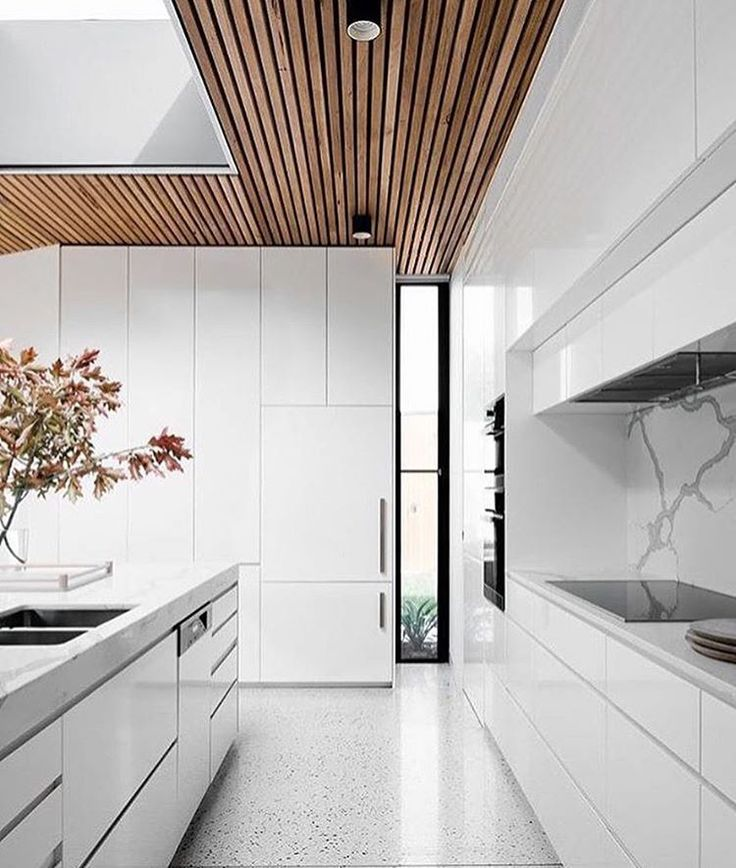 Kitchen: white cabinets, marble benchtops, marble splashback, pale light grey polished concrete floor, timber-panelled ceiling
