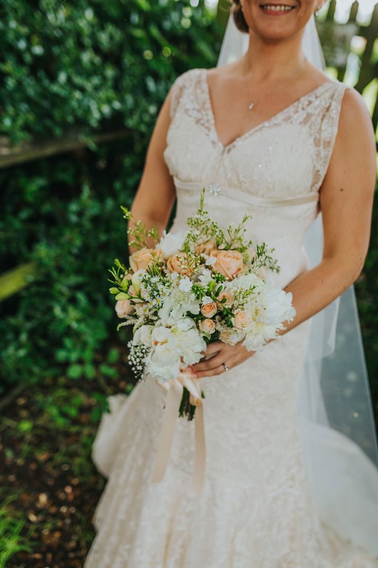 Lovely lace wedding dress with flowers by Eclectic Bliss Events. Photo by Benjamin Stuart Photography #weddingphotography #bride #weddingdress #eclecticblissevents #weddingday #countrywedding