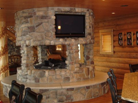 This 360 degree fireplace adds drama and seating in a golden eagle log home for the home - Incredible central fireplace ideas ...