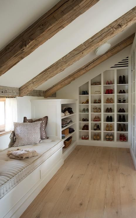 Walk-in attic closet features a sloped ceiling lined with rustic wood beams over angled built in shoe cubbies and sweater shelves next to a window seat.