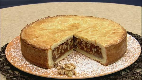 Engadine Torte - a Swiss dessert with thick lemon-zest scented pastry crust with eggs, filled with walnut-studded soft caramel before sealing shut in a springform pan.