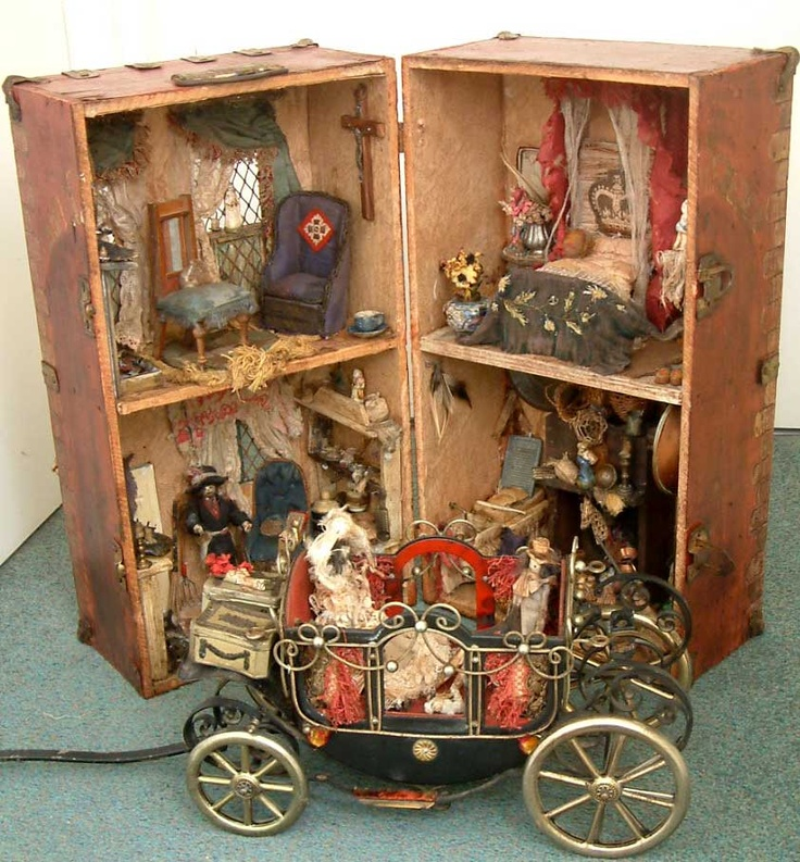 MINIATURE: This is an unusual dolls house in the shape of a wooden trunk, fully furnished with four homemade dolls and a quite regal looking musical iron carriage. Exact date is unknown
