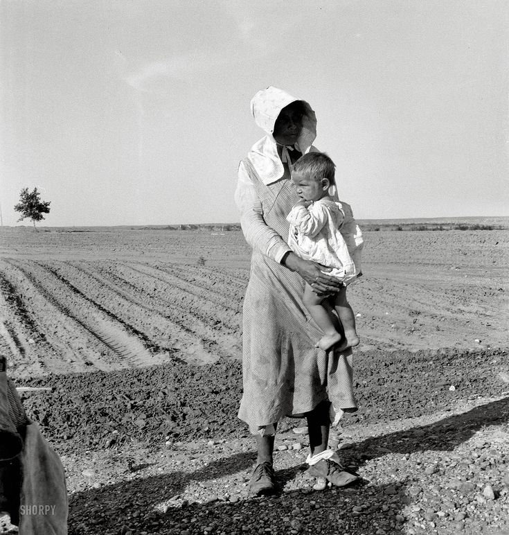 "May 1937. ""Mother and child of Arkansas flood refugee family near Memphis, Texas. These people, with all their earthly belongings, are bound for the lower Rio Grande Valley, where they hope to pick cotton."" by Dorothea Lange"