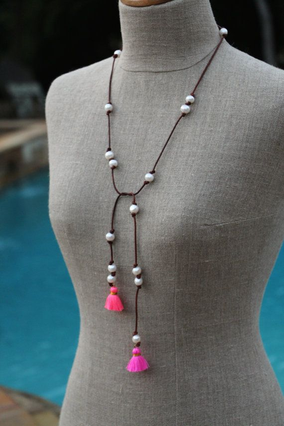 LOVE this one!! :)    A fun, white freshwater pearl on distressed leather lariat necklace, with two bright and happy cotton tassels for the