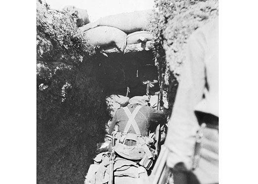 The barricaded end of a captured Turkish trench at Lone Pine after the battle on 10 August 1915. This image illustrates well the manner in which, after a portion of trench had been seized by the Australians, a new front line was created by the erection of a barricade in the trench itself constructed of sandbags and other material to hand. The Australian war Memorial's caption to this image states that the Australian soldier at the barricade was looking through a loophole down a Turkish…
