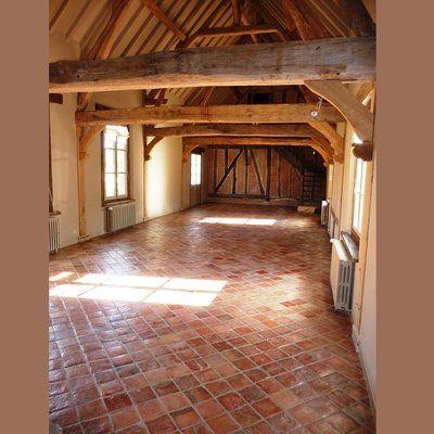 Salle carrelée avec des tomettes anciennes de couleur rouge, chez Vestiges de France.