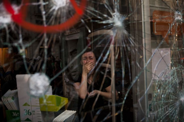 Mireia Arnau (39) reacts behind the broken glass of her shop, stormed by demonstrators clashing with police in Barcelona, during a general strike on 29 March.