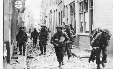 British troops move through the narrow streets of the Dutch town of Flushing on the look-out for enemy snipers in 1944