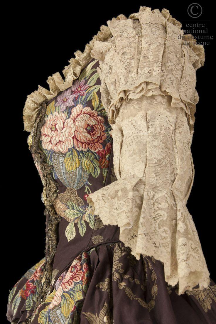 La Reine Marie Leszczynska - Comédie-Française RÔLE: La Reine Marie Leszczynska ARTISTES: Béatrix Dussane DESCRIPTIF COSTUME: Robe de style XVIIIe siècle en brocard marron à motifs fleurs, rose et or, dentelle ocre. Manches en lingerie et dentelle écrue. Pièce de corsage garnie de bijoux or et strass. ATELIERS DE FABRICATION: Indéterminé COMMENTAIRES: Les costumes de Mme Dussane ont été exécutés d'après les portraits de Van Loo et de Nattier, avec des étoffes anciennes de chez Fulgence et…